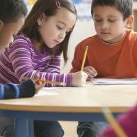 Three children at a classroom table with paper and pencil.