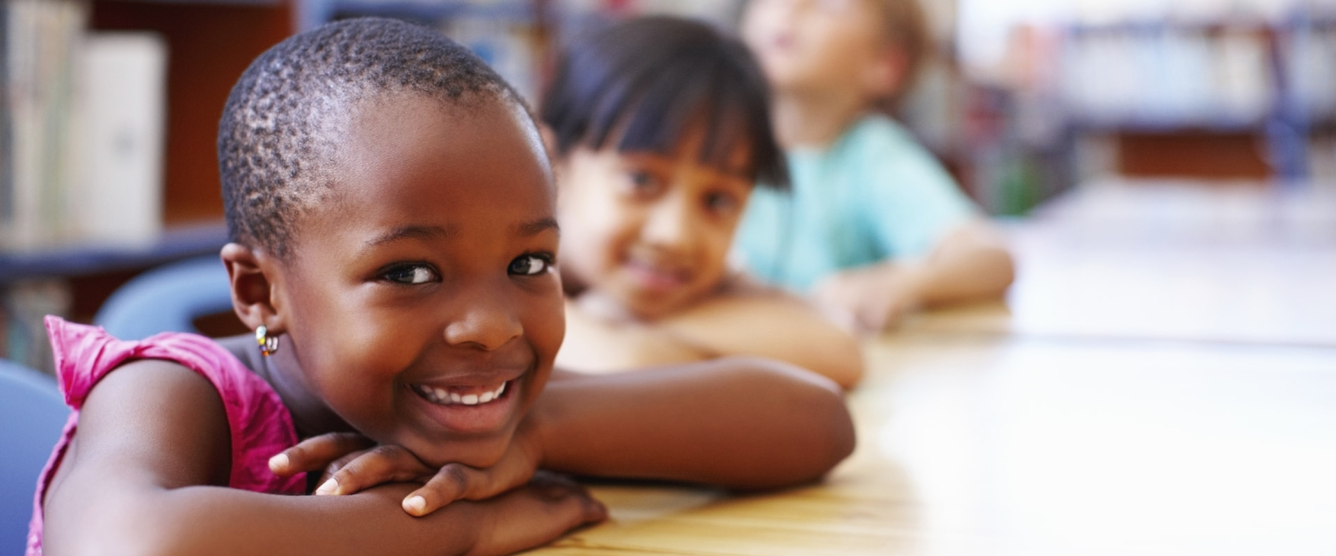 Young children sitting and smiling at their desks.