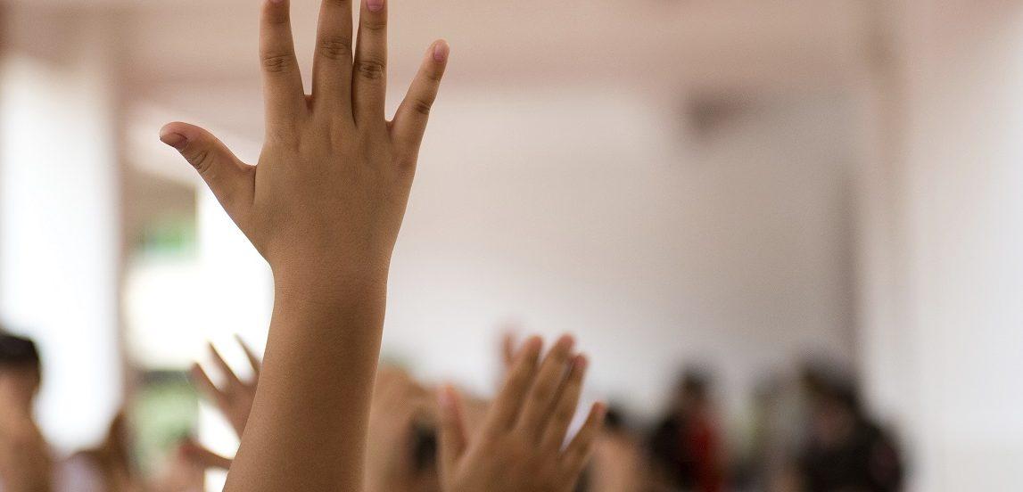 Image of children raising their hands.