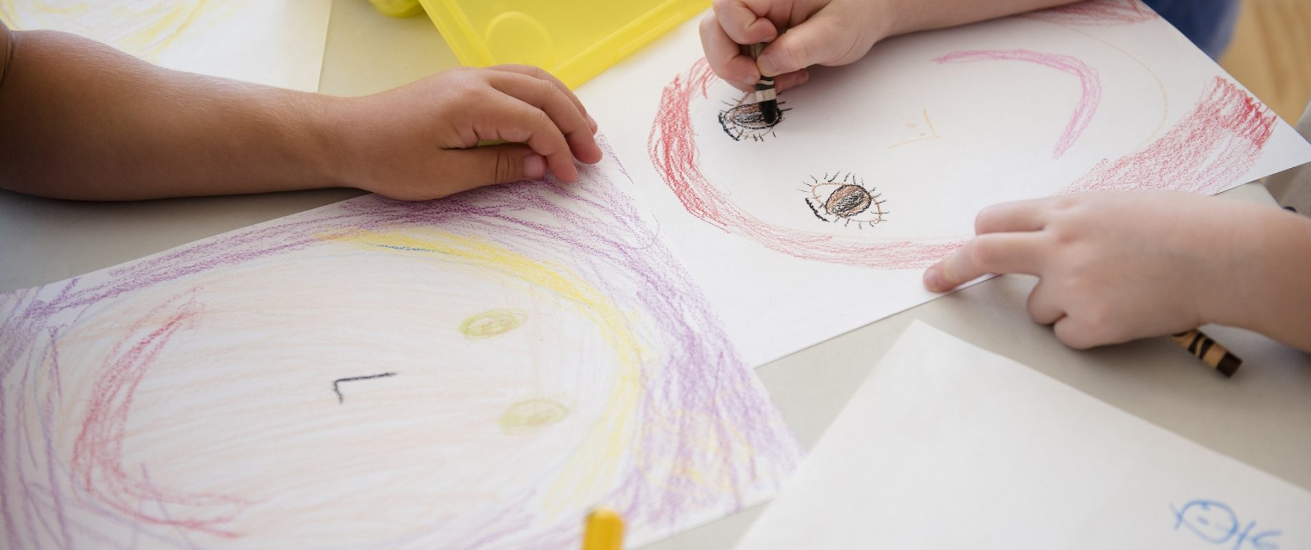 Young children drawing with crayons on paper in a classroom.