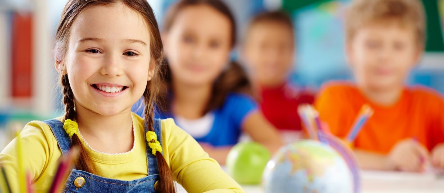 Preschool children smiling in a classroom.