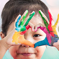 Preschool child making heart with painted hands.